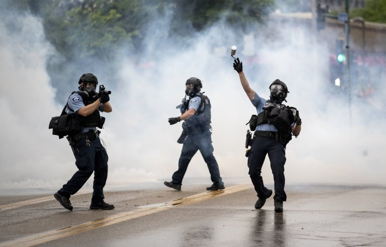 A police officer throws a tear gas canister towards protesters at the Minneapolis 3rd Police Precinct